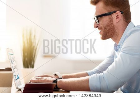 Diligent worker. Pleasant involved handsome man sitting at the table and using laptop while typing