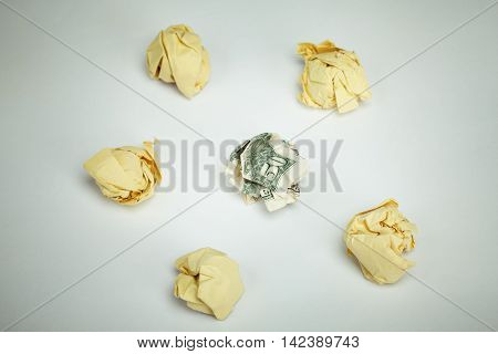 Dollar banknote surrounded by crumpled papers. Financial concept image. View above