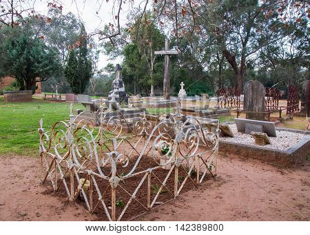 HENLEY BROOK,WA,AUSTRALIA-JULY 15,2016: Old cemetery with headstones, ornate fencing and large wooden cross at All Saints Church treed grounds in Henley Brook, Western Australia.