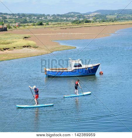 The Axe Estuary in Seaton during high tide with stand up paddlers