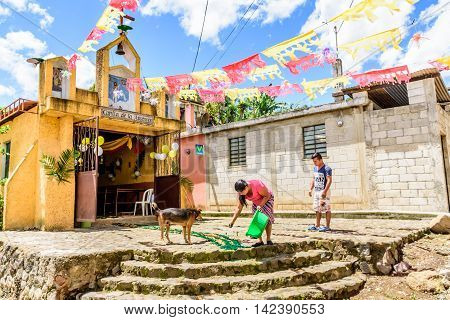 San Juan del Obispo Guatemala - June 26 2016: Local woman makes dyed sawdust carpet in front of chapel for procession part of St John's Day celebrations in small village named after the patron saint. Near Antigua, a UNESCO World Heritage Site.