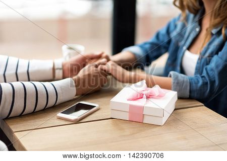 True feelings. Close up of hands of loving couple holding them together and sitting at the table while having a date