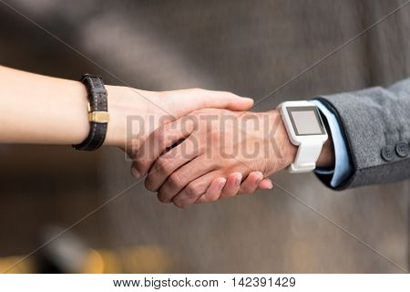 Deal. Close up of hands of pleasant colleagues shaking them while reaching common ground