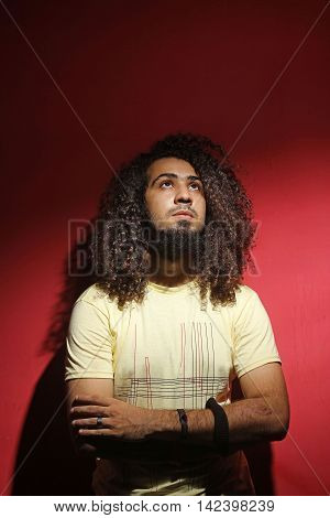 Sexy brunette young guy fashion and long beautiful curly hair against red background looking up
