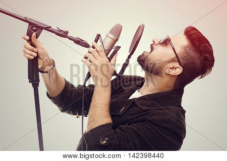 Talented young man wearing a brown coat and glasses singing a song in studio recording