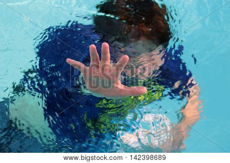 Drowning boy child in swimming pool reaching out with hand for rescue.