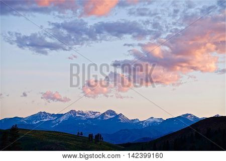Pink sunset clouds over snowcapped mountains ans trees silhouettes. North Cascades National park Winthrop WA USA.
