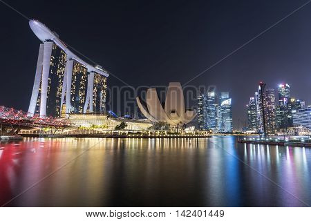 SINGAPORE CITY SINGAPORE - AUGUST 9 2016: Marina Bay Sands at night with The Helix Bridge and Art Science Museum Marina Bay located in the Central Area of Singapore Singapore on AUGUST 9 2016