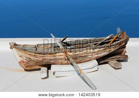 Old wooden rowing boat overlooking Santorini's bay