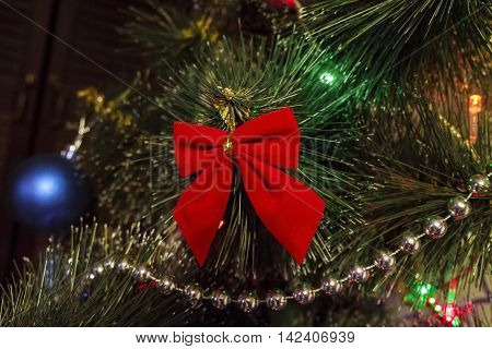 Red fabric bow decorate the Christmas tree. Photo with limited depth of field.