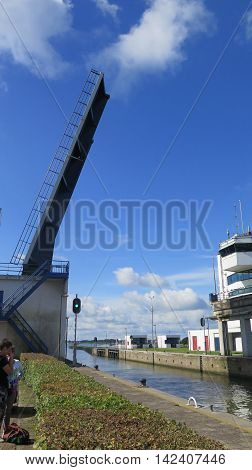 Opening lift bridge on canal sluice in Holland