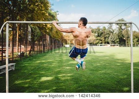 Male Athlete Doing Pull Ups, Chin Ups In The Park. Fitness Atheltic Man Working Out And Training In
