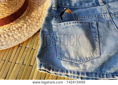 sunglasses in short blue jean back pocket and bamboo hat on sunny day
