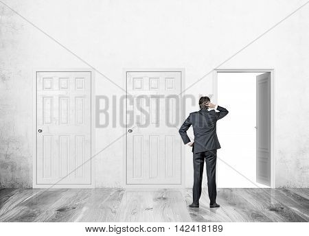 Man standing in concrete wall corridor with three doors. One open two closed. Concept of finding right way to solve problem.