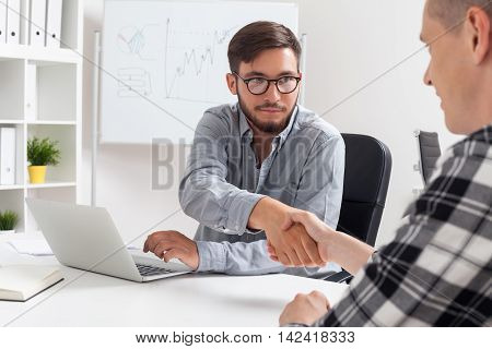 Two men shaking hands across table. Job interview with applicant. Concept of new exciting job opportunity.