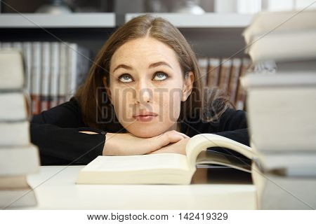 Cute Brunette Student Girl In Black Jacket Studying And Reading Textbook Or Manual In University Lib