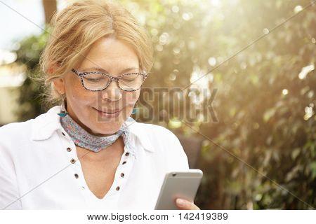 Headshot Of Good-looking Modern Blond Mature Woman Wearing Glasses, Messaging Her Grandson Via Socia