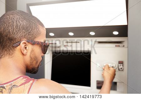 Man Withdrawing Cash From Automatic Machine Teller. Side View Of Young Dark-skinned Hipster In Sungl