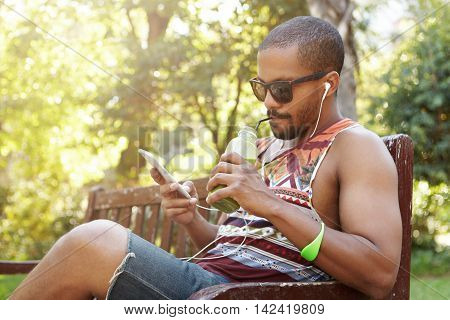 African American Man In Headphones Sitting On Bench In Public Park Listening To Songs On Cell Phone,