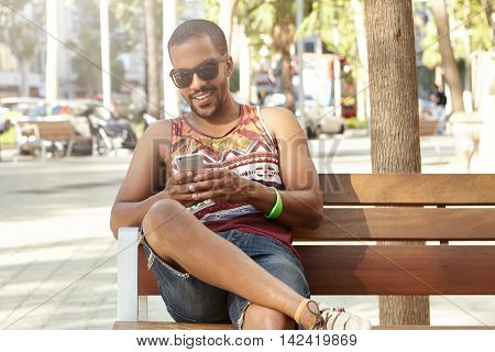 Stylish Tourist Relaxing In Park, Sitting In Shades Of Trees With His Gadget. African Man Surfing In