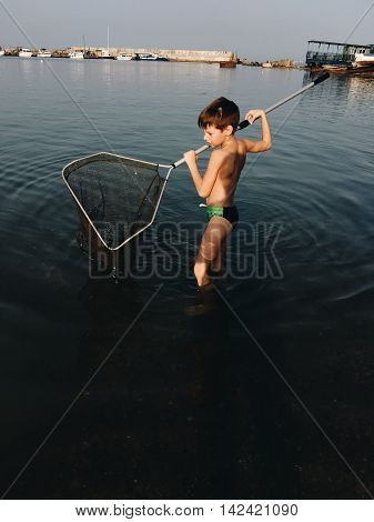 hot day in the bay of the little boy with butterfly net fishing