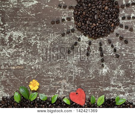 Sun shaped coffee beans and ground full of coffee with green leaves yellow flower and shape of heart