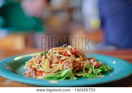 asian fusion food spaghetti and fried meat with basil leave, hot and spicy food