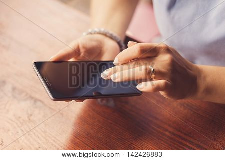 A woman is using her smart phone at a table outside