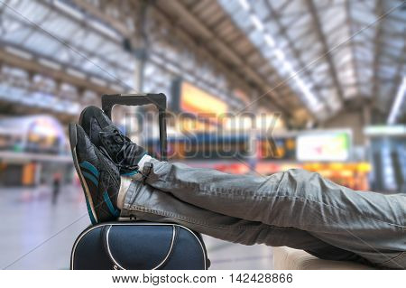 Delayed train concept. Tired passenger is waiting on train with baggage.