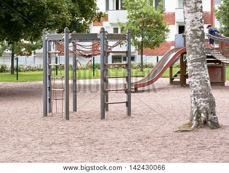 Children's playground with slide climbing frame and rocking at summer