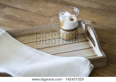 Glass of latte macchiato on a wooden tray
