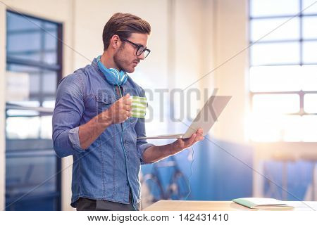 Business executive having coffee and looking at laptop in office
