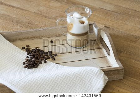 Glass of latte macchiato and coffee beans on a wooden tray