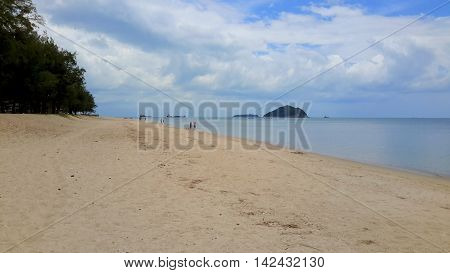 billowing cumulus clouds over a flat sea, with two islands, several ships on the horizon, dark pines on the left, sandy beach, Songkhla, Thailand