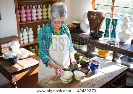 Female potter arranging bowl on worktop in pottery workshop