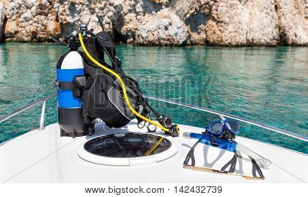 Scuba diving equipment on a boat in front of the emerald waters of the mediterranean sea
