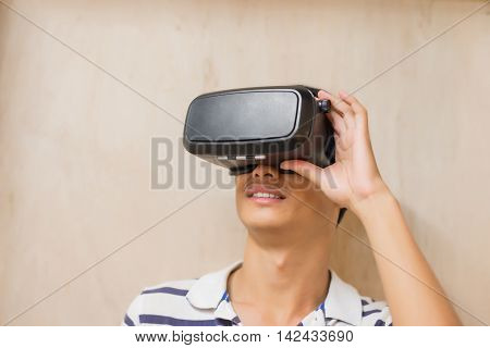man wear virtual reality headset happily with Brown wall asian