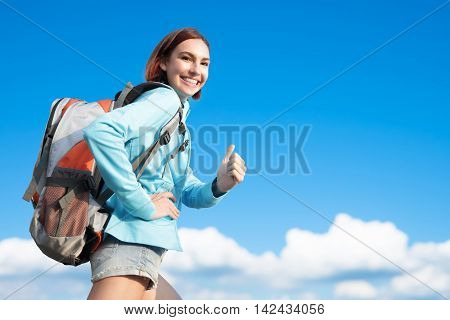 happy woman mountain hiker go to travel and show thumb up with blue sky and white clouds caucasian