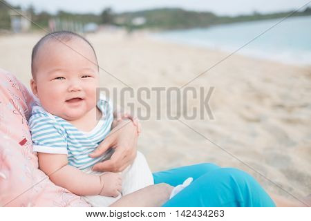 cute baby smile happily in adult arms in the beach asian