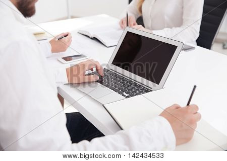 Businessman typing on keyboard and making notes simultaneously. Concept of multitasking importance for business. Mock up