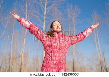 Woman in pink greeting the sun with her wide open arms in winter. The sunshine is very bright.