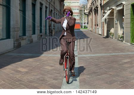 Woman drinks coffee pedaling a unicycle, outdoor scene