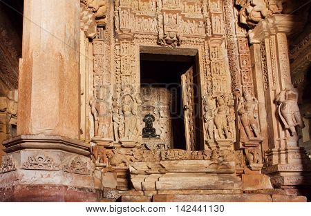 Hindu god in darkness of ancient temple of Khajuraho with carved stone walls and corridors India. Khajuraho Monuments built between 950 and 1150.