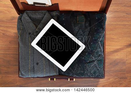 Vintage travel background. Top view of old suitcase with clothes on wooden floor with tablet computer with copyspace. Retro style.
