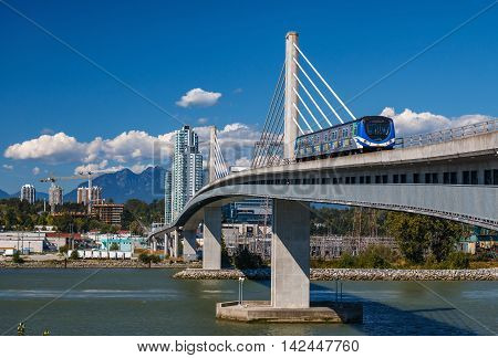 VANCOUVER CANADA - AUGUST 11 2016: Canada line train passes bridge on August 11 2016. The Canada Line is Vancouver's new rapid transit rail link connecting airport to downtown Vancouver.