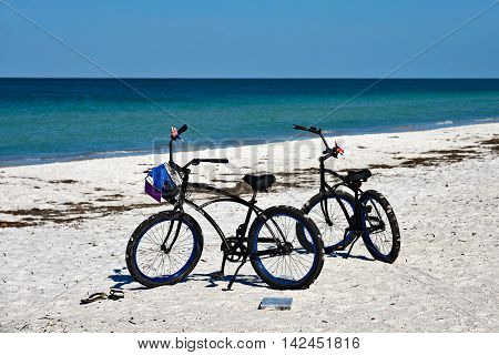 Two Bicycles with Baskets parked on the SAndy Beach of Anna Maria Island Florida