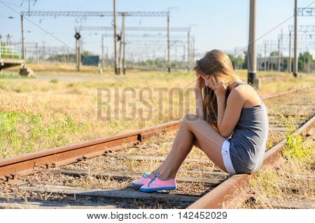 Sad girl teenager sitting on rusty rail track outside the town. Escape to be alone