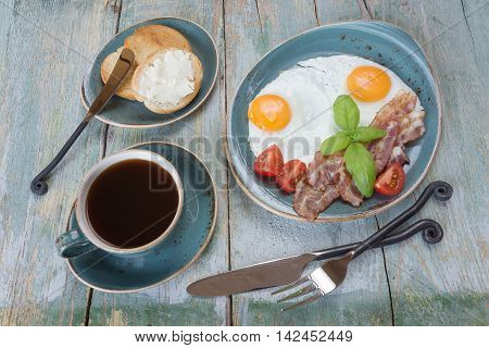 Breakfast consists of fried eggs bacon tomato toast and a cup of coffee on the old wooden table; top view flat lay