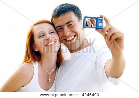 An attractive couple together on the white background, taking a selfportrait.