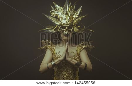 Golden power, brunette goddess dressed in gold lace dress. concept deity and faith